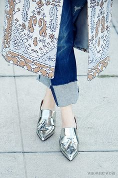 Cuffed jeans are worn with a jacquard coat and metallic loafers