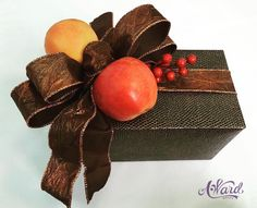 """Wrapped this present for a couple celebrating their 4-Year Anniversary, which is the year to give """"Fruit"""". The  warm colors of the fresh apple and blood orange gift toppers play nicely against the crushed stain ribbon and snake skin textured wrapping paper."""