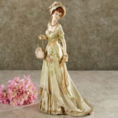 """Dressed in her finest for a day about town, this elegant lady is an image of pure Grandeur. This resin lady figurine depicts a woman lavishly adorned with a pale green hat and dress, decorated with dainty florals of peach, pink, and yellow. A rounded pink purse is on her arm. A yellow sash, a bracelet, and a necklace complete her elegant ensemble. Decorative lady figurine is 7""""Wx6""""Dx12.5""""H.    • Flowers on her gown have gem embellishments  • Lady figurine is intricately detailed"""