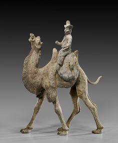 Chinese early Tang Dynasty (618-917 c.e.) pottery model of a Bactrian camel with well detailed features, the beast in a walking stance, with head thrown up and mouth agape; together with original separate saddle with bearded foreigner riding and wearing an unusual hat, probably a hunter; the saddle sides with some animals.