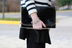 Sweater weather -- Striped sweater, leather skirt, black clutch