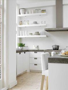 Det ljusa köket har en arbetsbänk i betong, och har extra breda arbetsytor. Skåpen av vitlaserad ek...