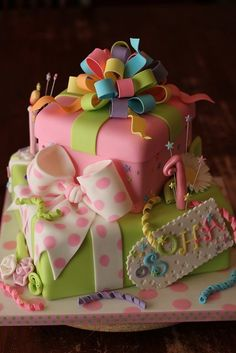 Bright pink and rainbow color baby shower cake idea - looks like presents stacked up - cute!