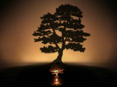 Lumen Tree Shadow Lamp, battery-powered flameless candle casts an enchanting shadow from a tiny, stainless steel pine tree. GetdatGadget.com/lumen-tree-shadow-lamp-plant-tree-room/