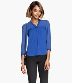 V-neck blouse in satin with a yoke and sleeves in airy woven fabric. Concealed buttons at top. Long sleeves with slightly puffed shoulders and buttons at cuffs.