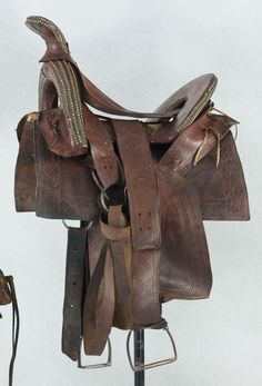 Navajo Man's Saddle - ca.1900 (Side View Detail)  The man's saddle has the traditional upswept horn and iron stirrups.  Shows typical brass stud decoration.