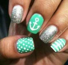 Sea foam green nails with white polka dots, white stripes and white anchor designs and silver glitter nails.