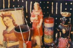 Altar: The traditional Catholic image of St. Barbara that has been adopted by syncretic Santeria  is on the left; the statue of the young saint is in the center. There are unconsecrated red and white Chango beads, the kind you buy in a botanica, rather than receive in a ceremony, and a handcarved wooden mortar. There's also a symbol of Chango; a little Santa Barbara scapular; and the traditional 7-day Seven African Powers candle showing her at the top.
