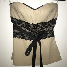 A strapless tank top (corset look alike) It's strapless beige shirt, with black lace around the middle and a ribbon! Nicely fitted. Size M (4-6) Tops Tank Tops