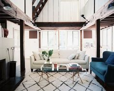 Bright and open living room with exposed wooden beams and a Moroccan rug