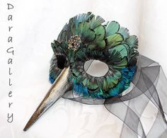 A multitude of iridescent copper green Lady Amherst and bright blue Peacock body feathers are used to create this hummingbird mask. Order your