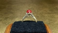 This stunning vintage Art Deco ring would be perfect for any collection. Crafted with 14K yellow gold, this dainty At Deco ring features a gorgeous vibrant red coral sphere and an intricately detailed filigree seashell design that encompasses details form the late Art Nouveau and early Art Deco Era