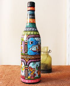Pattachitra painting on a bottle/ OUATT Market  The beautiful and intricate Pattachitra paintings on this tall glass bottle in a multitude of bright colors in red, blue and gold depicts the Pattachitra - Saura (Tribal Painting) of Odisha in East India and displays the fine and delicate work and paintings of mythological figures, dieties and gods.