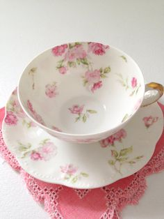 White tea cup and saucer lined with delicate pink flowers.