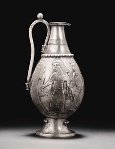 I think this is the earliest clothing I've ever seen from Persia. Also, clothing looks like it has Egyptian influence, including the protective aprons. A RARE AND IMPORTANT POST-SASANIAN OR EARLY ISLAMIC SILVER EWER, PERSIA, 8TH CENTURY