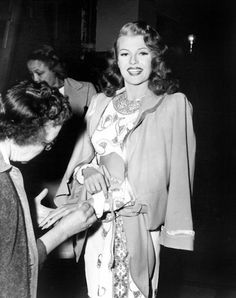 Rita Hayworth having her wardrobe adjusted on the set of GILDA