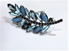 ITEM # 121648  Brooch consists of 3 large deep blue faceted glass navettes, 7 long spiky aquamarine blue faceted glass navettes, 4 blue-black moonstone cats eye navette cabochons, a medium sapphire blue faceted glass round, and 17 small sapphire blue faceted glass round accent stones that run through the middle to make the stem. All navettes are open back. Brooch is set in a silver rhodium plating.  Brooch measures 3 in length and 1 at its widest.  Condition: Very good antique condition with…
