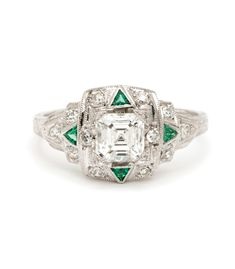 A stunning vintage engagement ring with a modern edgy appeal. This platinum art deco style ring features a 0.75ct asscher cut diamond center (G, VS1) set within a square shaped frame, with single cut diamond accents and is highlighted with 4 triangular synthetic emerald accents. We are in love with the details of this geometric design and this mesmerizing center stone.