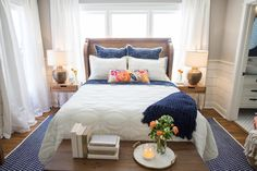 Just love the white and navy bedroom linens, shiplap, oversized lamps, and the cute table at the foot of the bed.