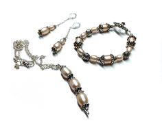 Ensemble #258 ($50) Collier de 16½ pouces (44 cm) plus la breloque (10 mm X 60 mm): -Perles d'eau douce de 9 mm x 12 mm Bracelet: 7½ pouces (19 cm): -Perles d'eau douce de 9 mm X 12 mm -Perles d'eau douce de 9 mm X 7 mm -Billes de métal de 12 mm Boucles d'oreille 2 pouces (5 cm): -Perles d'eau douce de 9 mm x 12 mm -Perles d'eau douce ronde de 10 mm -Chaine de métal anti-ternissement. Fait main