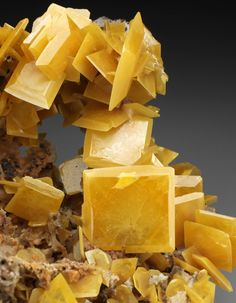 A WONDERFUL Wulfenite, one of the best known from Touissit. The delicate yet razor sharp crystals form bright yellow lustrous squares with beveled edges, framing the cavity.