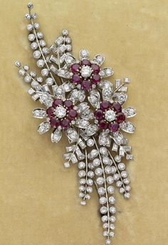 A ruby and diamond brooch, 1940s. Of stylised flowerspray design, the three flowerheads each centrally set with a round brilliant-cut diamond, framed by six circular-cut rubies, the petals and fronds set with further round brilliant and baguette-cut diamonds.