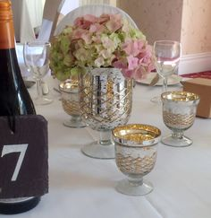 Hand-made slate table numbers painted with Annie Sloan paint, mercury glass vases filled with hydrangeas with mini vases used for tealights. By Eleanor Gail.