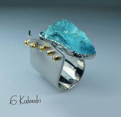 G. Kabirski ring of awesomeness. Uncut aquamarine in zaggity edge bezel and pop out sideways bezels on sheet of white.