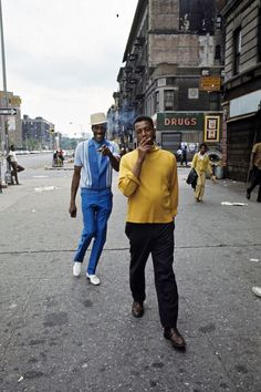 An African American man smokes while walking down a street. A second man in a blue hat stands behind him pointing at the camera, 1970  Photo credit: Jack Garofalo — at Harlem N. Y.