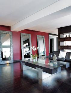 Contraste de color ... La única concesión entre la gama oscura y el blanco roto es la pared granate del salón. Tres grandes espejos con marcos de cristal craquelado amplían visualmente el espacio