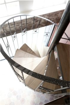 DH84 - SPIR'DÉCO® Art Déco - modèle déposé. Escalier hélicoïdal d'intérieur métal et bois pour une décoration Art Déco. Marches avec plateaux bois massif incrustés, contremarches ajourées avec découpe décorative. Limon découpé type crémaillère en tôle roulée. Rampe à l'ancienne avec barreaudage en fer carré fixé à l'anglaise contre la crémaillère y compris motif en fer forgé + option main courante débillardé en fer plat martelé. Finition : acier brut patiné. © Photo : Nicolas GRANDMAISON.