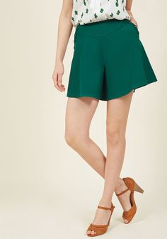 <p>With every twist and twirl you give in these rich green shorts, your retro aesthetic simply can't be missed! Flared, flowing fabric provides this high-waisted pair the look of a skirt but the carefree wear of pants, while button-framed pockets ensure a seamless blend with your pre-existing pieces.</p>