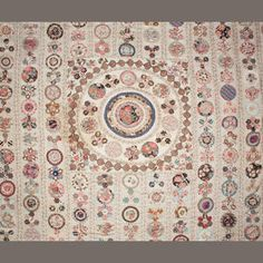 Worked in hexagon and circle applied patches to a cream ground, with a circular central design, worked in early to mid 19th century floral and patterned dress fabrics in shades in reds, blues and browns, with some nice examples of early floral block printing, in a good general condition. 300x270cm, Bonhams
