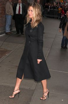 Jennifer Aniston Strappy Sandals - Jennifer's strappy black evening sandals looked sexy with her black calf-length trench coat. This minimalist style is a great staple shoe that can go with a variety of evening looks.