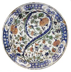 A LARGE IZNIK POTTERY DISH   OTTOMAN TURKEY, EARLY 17TH CENTURY   With sloping rim and rounded cavetto on short flat foot, the gilt and painted decoration with a long curled saz leaf among roses, hyacinths and tulips