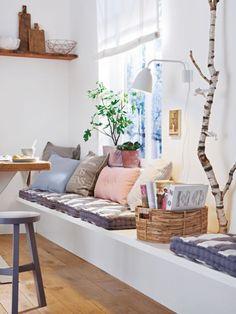 Drewniane ławki i zabudowane siedziska z poduchami przy stole w aranżacji kuchni i jadalni