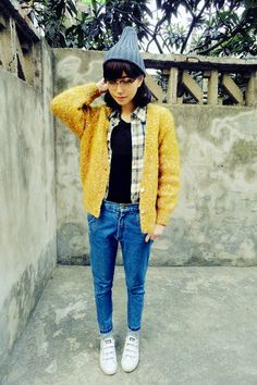 beanie, yellow cardigan on plaid shirt and black tee, denim and white sneakers. love the specs.