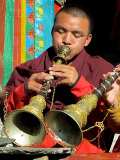 ABuddhistmonk playing a reed horn in Nepal