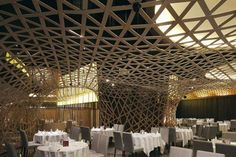 A woven net of bamboo creates a curved suspended ceiling inside this restaurant in Hangzhou, China by architects FCJZ.
