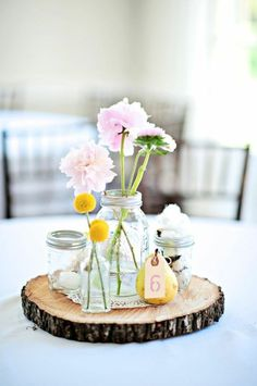 simple centrepiece;  this is what I want. floral piece in mason jar and different items surrounding. Items from our house, parents homes. etc. table numbers order from anthropologie wedding (long stick sparkle numbers)