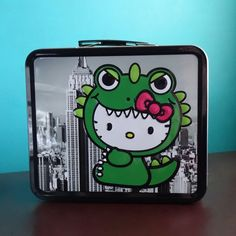 "Carry your food in style with this cute Kittyzilla tin lunch box by Loungfly x Hello Kitty. Comes with collapsible plastic handle and metal latch closure. Dimensions: 7""H x 8""W x 4""D"