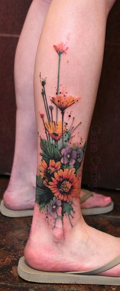 Sunflower watercolor tattoo on leg, would not get one here or this big but I like the style.