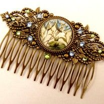 This large water lily hair comb in antique-style is a beautiful accessory for festive updo. It consists of bronze metal. In the middle there is a jewelery holder with a hand-crafted glass cabochon which shows a beautiful motif with water lilies. The hair comb is also decorated with sparkling rhin...