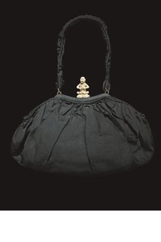 An early ruched and pleated silk bag with an ivory lock carved in the form of a monkey.   - HarpersBAZAAR.com