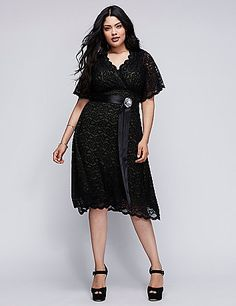 Retro Glam lace dress by Kiyonna channels vintage inspiration in scalloped lace with a satin sash. Soft stretch lace skims curves for easy-wearing elegance, with a shirred surplice neckline and sheer elbow length sleeves. An optional rhinestone brooch adds a sparkling finish. Fully lined. lanebryant.com