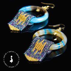 Wyjątkowe – proste w formie, a zarazem efektowne kolczyki z linii TOKEN. Wykonane z koralików Miyuki Delica na obręczach z agatu. Wykończone kryształkami Swarovski, na metalowych biglach w kolorze złotym.