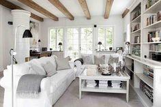 biały salon z drewnianymi belkami na suficie,skandynawski salon z drewnianymi belkami,jak urządzić skandynawski salon z drewnianymi belkami,białe wnętrza z drewnianymi belkami,aranżacja salonu w skandynawskiej tradycji z belkami na suficie