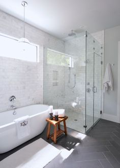 White bathroom, free standing tub, monogrammed towel, grey floor tile, glass shower, pendant lighting above tub | Lilli Design