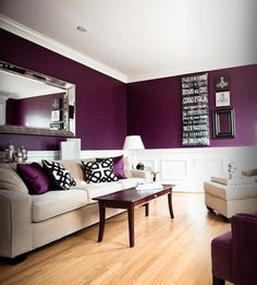 Rich plum room that is brightened with white wainscoting, beige couch and light flooring.