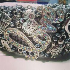 Brazalate tejido en Gris Plata con dijes en plata antigua y cristales , asi como.medallon LOVE con cristalesswarosky 4 cm de ancho